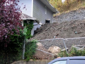 Retaining Wall gone wrong - dirt freely piling up angainst the house