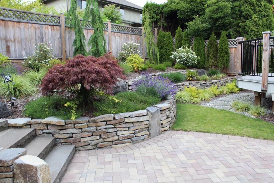 Natural stone wall around a landscaped garden with shrubs, flowers and trees.